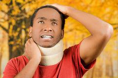 Injured young positive black hispanic male wearing neck brace, holding hands in pain around support making faces of. Agony, yellow abstract background Royalty Free Stock Images