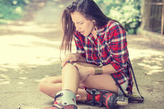 Injured young woman suffering from pain sitting on the ground. In-line skating injured young woman suffering from pain sitting on the ground outdoors on summer Royalty Free Stock Photography