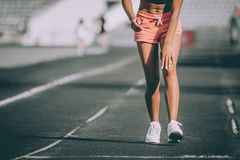 Injuries - sports running knee injury on woman. Grey background stock photo