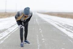 Injuries - sports running knee injury on woman. Winter marathon. Royalty Free Stock Image