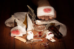 Injury hands behind a broken bottle. First aid. Injury hands behind broken bottle, bandages, cotton wool, adhesive tape Stock Photos