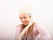 Injury of head. Head of kid with injury covered with bandage - smiling wounded blond girl in pink blouse taking off the bandage stock photos