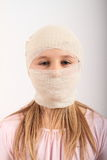 Injury of head. Head of kid with injury covered with bandage - wounded blond girl in pink blouse royalty free stock photo