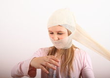 Injury of head. Head of kid with injury covered with bandage - wounded blond girl in pink blouse taking off the bandage royalty free stock images