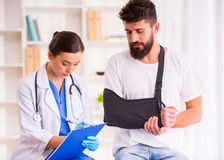 Injury man in doctor. Injury hands. Young men with injured hands. Young women doctor helps the patient royalty free stock images