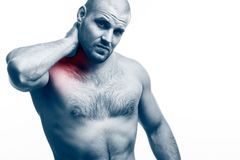 Injury of the neck. Young bald man sportive physique stretched and clings to a sick neck on a white isolated background. Stretching the neck stock images