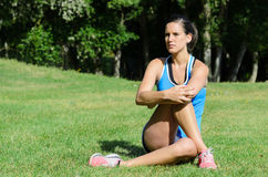 Injury Prevention. Young female athlete stretching for injury prevention sitting on grass in a park Stock Image