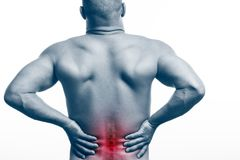 Injury of the spine. Young bald man sports physique holds a sick back on a white isolated background. Fracture of spine stock image