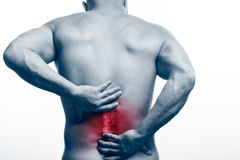 Injury of the spine. Young bald man sports physique holds a sick back on a white isolated background. Fracture of spine stock images