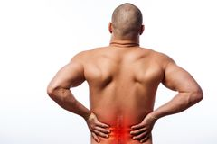 Injury of the spine. Young bald man sports physique holds a sick back on a white isolated background. Fracture of spine Royalty Free Stock Photo