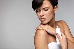 Injury Treatment. Beautiful Woman With Neck Pain Applies Cream Royalty Free Stock Photo