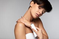 Injury Treatment. Beautiful Woman With Neck Pain Applies Cream Stock Photo