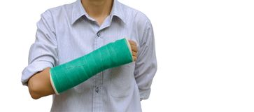 injury woman broken arm with green cast on arm standing on white stock photos