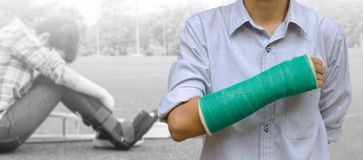 Injury woman broken arm with green cast on arm standing on background injury woman sitting with arm splint and holding wooden. Crutches stock photo