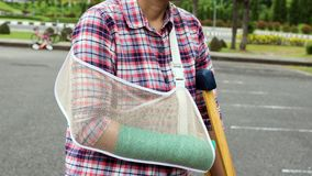 Injury woman with broken arm wearing an arm sling and green cast. On arm standing and using  wood crutches Stock Image