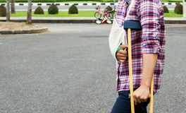 Injury woman with broken arm wearing an arm sling and green cast. On arm standing and using  wood crutches Stock Photo