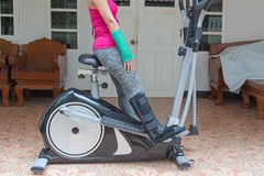 Injury woman wearing sportsware with green cast on hand and arm, black splint on leg sitting on exercise bike at home, body. Injury concept stock photos