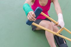 Injury woman wearing sportswear  painful arm  and leg with gauze. Bandage, arm cast and wooden crutches sitting on green floor Stock Photo