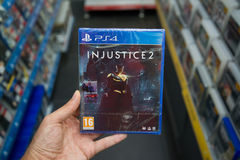 Injustice 2. Bratislava, Slovakia, june 15, 2017: Man holding Injustice 2 videogame on Playstation 4 console in store Stock Photos