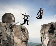 Injustice in business competition. Man jumps between two mountains before the men with a heavy ball obstacle Stock Photo