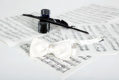 Ink bottle, feather, bow-tie and notes Stock Image