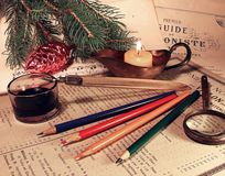 Ink and Christmas. The still life consisting of an inkwell, the pencils, burning Royalty Free Stock Photo