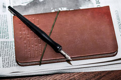 Ink dip pen on the notebook Royalty Free Stock Photography