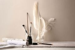 Brushes, feathers in glass ink bottles, pen, paper rollers with ink drawing of graphic, calligraphy. Ink drawing tools of graphic or calligraphy on white wood stock image