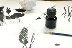 Ink Drawing work place. Jar of black Ink and thin brush on the table. Ink hand drawing, sketches Royalty Free Stock Image
