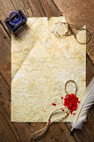 Ink, feather, glasses and red sealing wax on old vintage paper. On old wooden table Royalty Free Stock Images