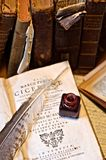 Ink and feather on old books and writing stuff Royalty Free Stock Images