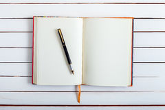 The ink handle lies on empty page of a notebook. Royalty Free Stock Image
