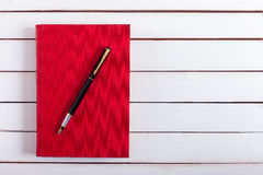 The ink handle lies on red book hard back. Royalty Free Stock Photography