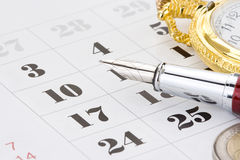 Ink pen and coin money on calendar Royalty Free Stock Photos