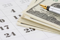 Ink pen and dollar money on calendar Stock Image
