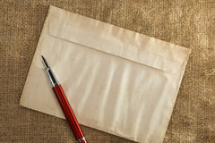 Ink pen at envelope on vintage sack background Stock Photos