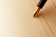 Ink pen on lined paper. Closeup of the nib of an ink pen against lined paper royalty free stock photo