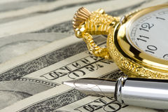 Ink pen and watch on dollar banknotes Stock Images