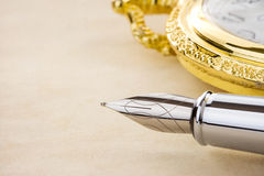 Ink pen and watch on parchment Royalty Free Stock Photos