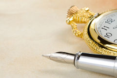 Ink pen and watch on parchment background Stock Photo