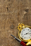 Ink pen and watch on wood Royalty Free Stock Photography