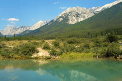 Ink pond and rocky mountains Stock Photos