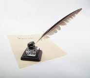 Ink pot with goose quill on letter paper Royalty Free Stock Images