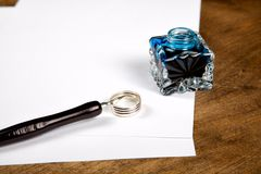 Ink pot and quill with sheets of paper Stock Images