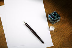 Ink pot and quill with sheets of paper Stock Image