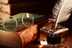 Ink Pot And Spectacles. Vintage still life. Old spectacles on book near glass inkwell with quill pen Royalty Free Stock Image