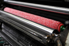 Ink rollers on offset printing machine. Opened offset printing machine with ink rollers with special red wetting roller. Print industry concept royalty free stock photos