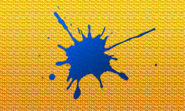 Ink splash on yellow board. Blue ink splash on a mainly yellow board covered by tiny white dots Royalty Free Stock Photos