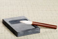 Ink stone and calligraphy brush. Closeup of an ink stone and calligraphy brush on a bamboo mat royalty free stock image