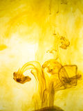 Ink swirl in a water on yellow background. The paint splash in the water. Soft dissemination a droplets of colored ink Royalty Free Stock Photos